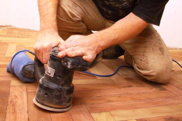 Шлифовальной машиной обработать деревянный пол для гладкости поверхности